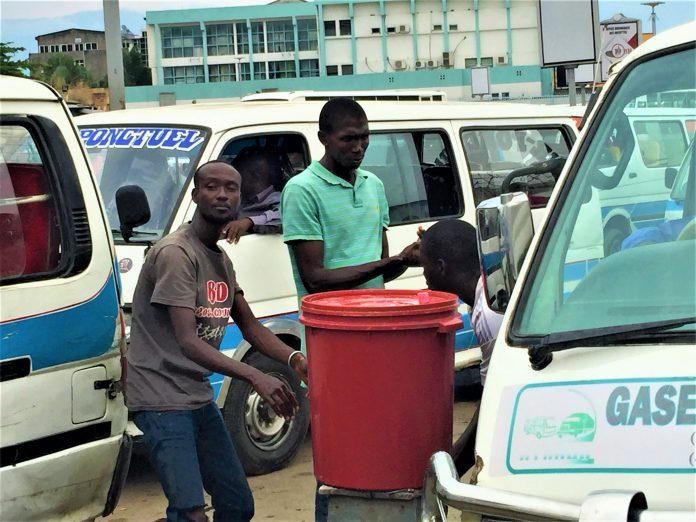 Les passagers se lavent un à un avant d'entrer dans les bus